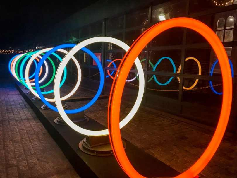 A row of several circles lighting in different colors as part of Georgetown's GLOW exhibit.