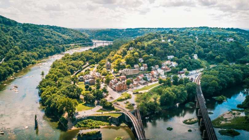 A high point view of a quant city called Harpers Ferry with a river and surrounding trees adjacent to the town.