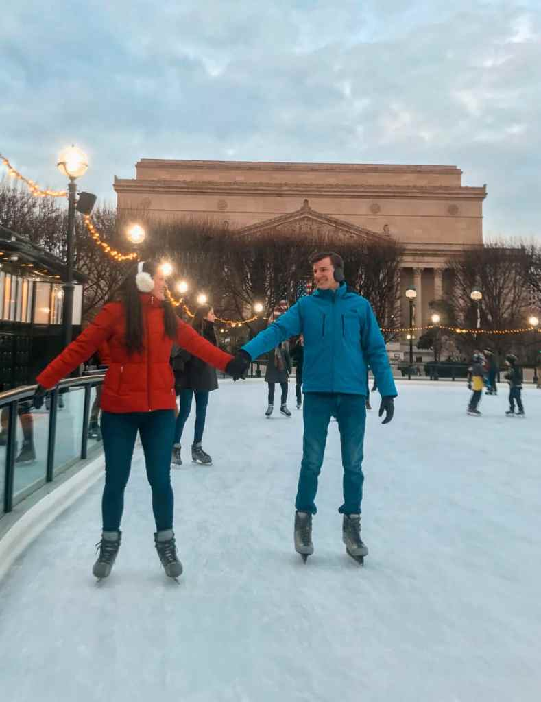 A cute couple holding hands while ice skating at the National Gallery of Art Sculpture Garden in Washington D.C. in the winter.