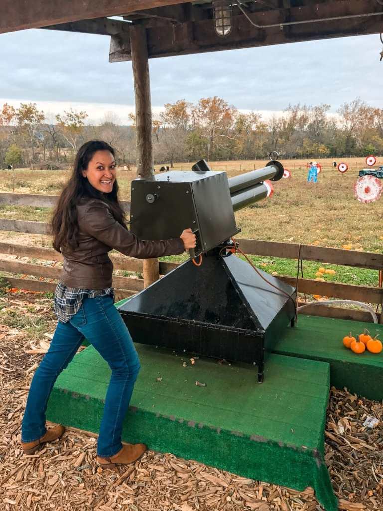 A woman posing while shooting from a pumpkin blaster at a farm near Washington D.C. in the fall.