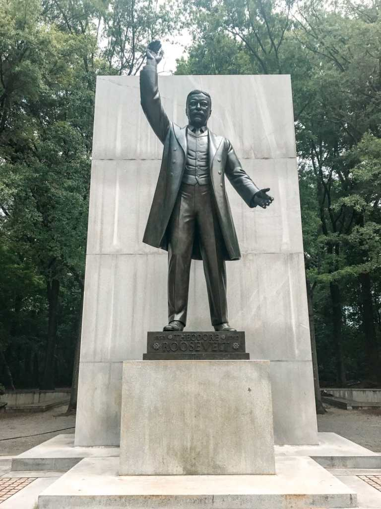 A statue of Theodore Roosevelt raising his hand as a memorial