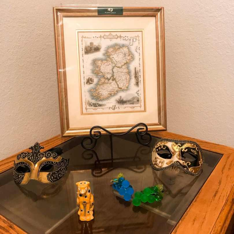Travel souvenirs of an Ireland map, Venice masks, Murano grapes, and a glass cheetah. Collecting souvenirs is a great way to save travel memories.