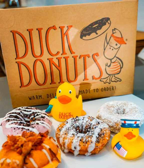 Powdered sugar and glazed cake donuts with little yellow rubber ducks next to the donuts. A cardboard box background with Duck Donuts on it.