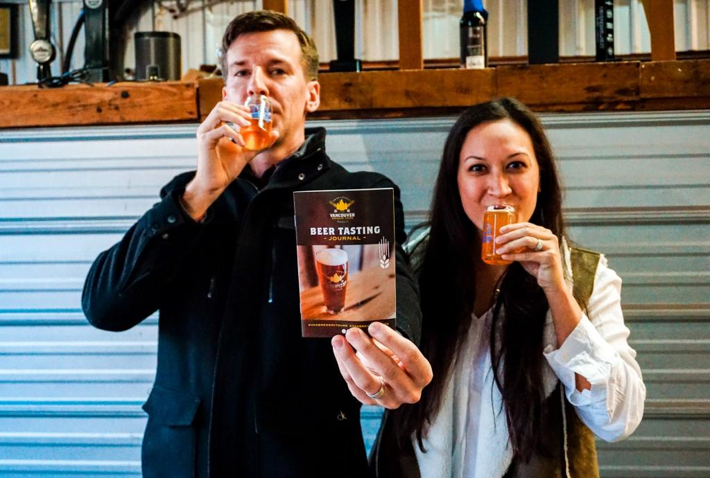 A couple sipping on beer while holding a pamphlet from Vancouver Brewery Tours.
