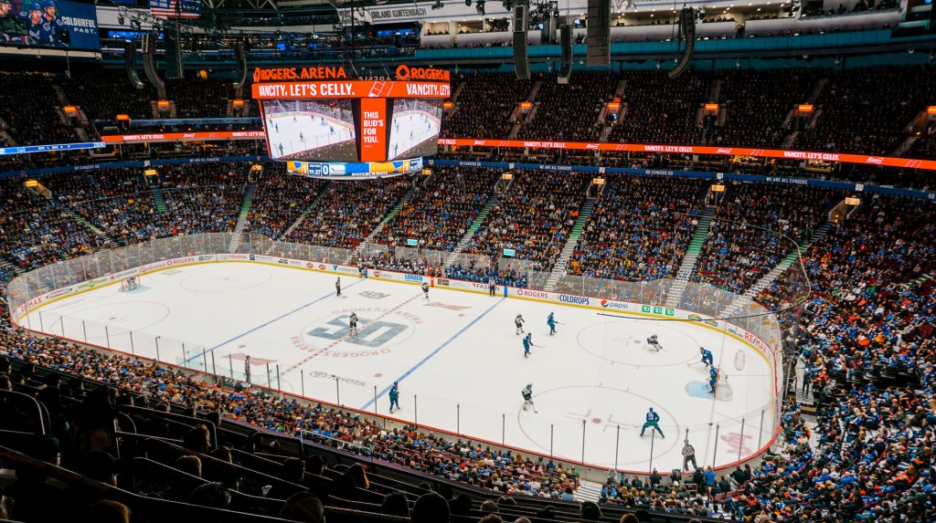 A side shot of inside Rogers Place Stadium during a Canucks hockey game. The photo shows two teams playing on the ice rink with a crowd full of people.