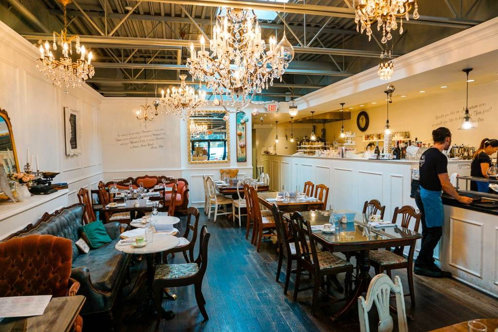 An inside look of Neverland Tea Salon with its whimsical antique decorations, mix matched chairs and tables, hanging chandeliers, and more.