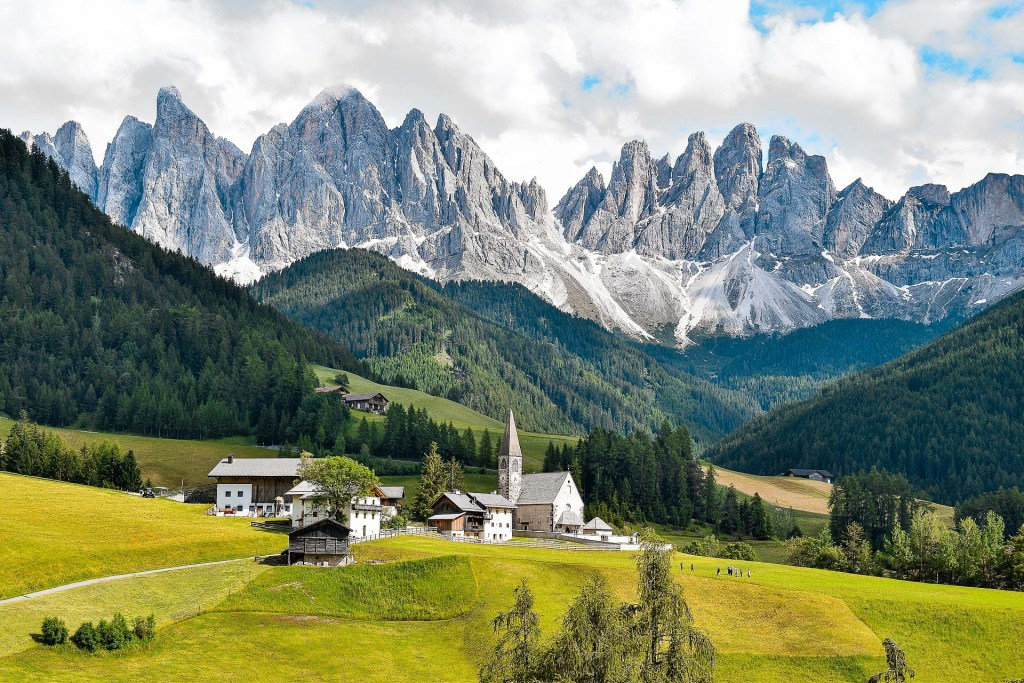 A beautiful landscape of the dolomites in Italy - a must see for any Italy bucket list. The photo shows a a mountain range in the backdrop with rolling green hills and a small village.