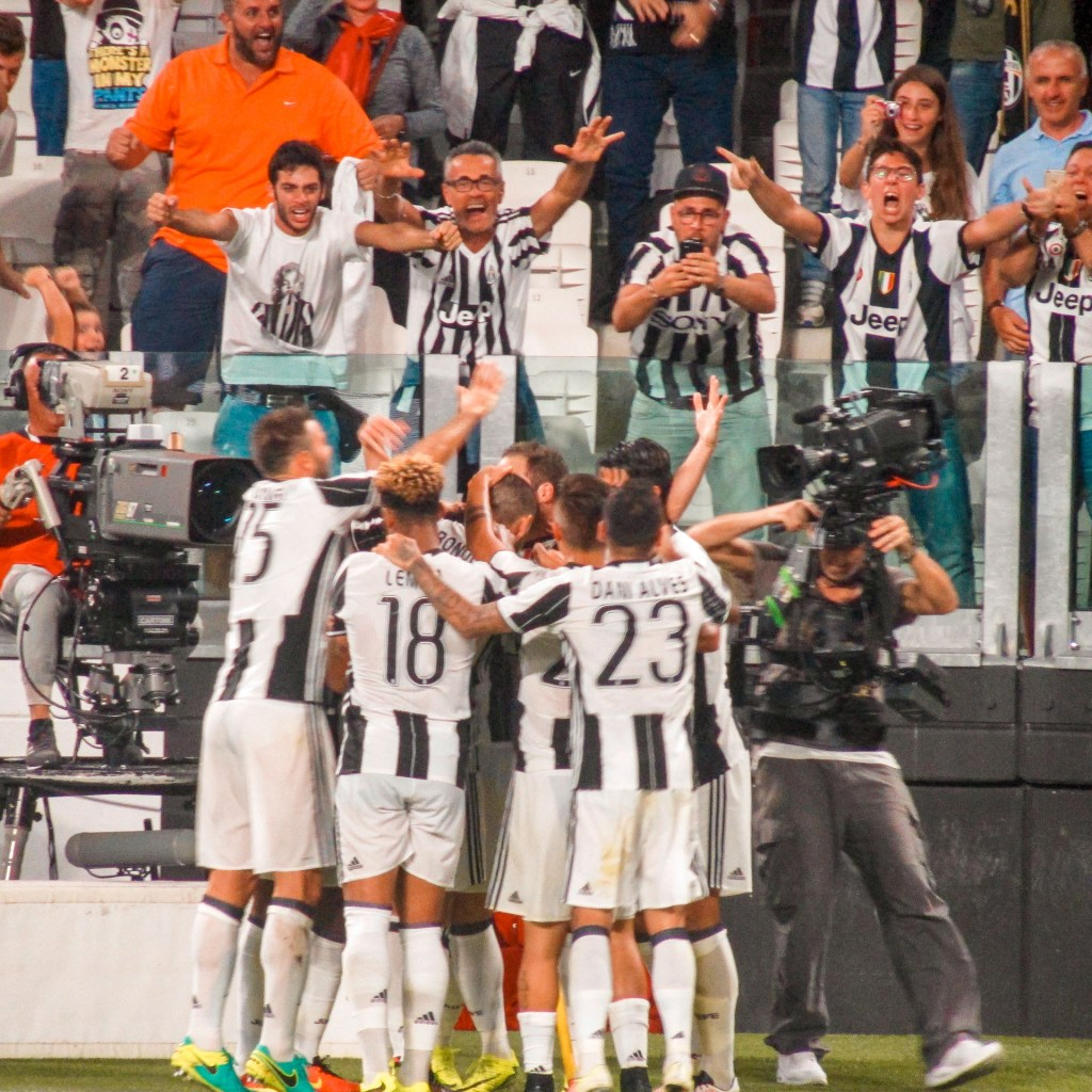 A crowd cheering on the Juventus team with players huddled around each other celebrating a goal.