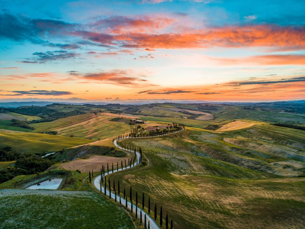 A sunset photo of Tuscany's Val d'Orcia with rolling hills and a blue-orange sky.