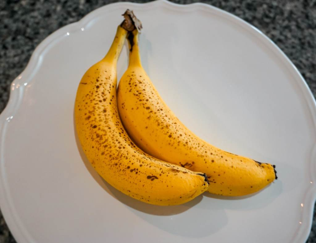 Two ripe bananas - bright yellow with brown spots, on a white plate.