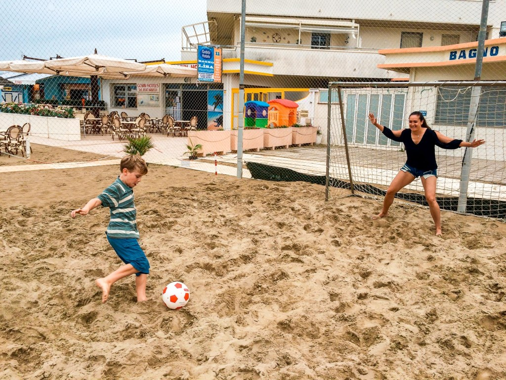 A little boy kicking a soccer ball at his older cousin in goal in Gatteo a Mare, an awesome beach town in Italy.