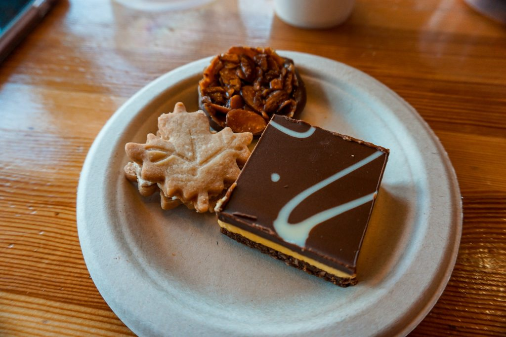 A plate with three different desserts - florentine, maple leaf buttercream cookie, and Nanaimo bar. These are some of most popular desserts you must eat in Vancouver.