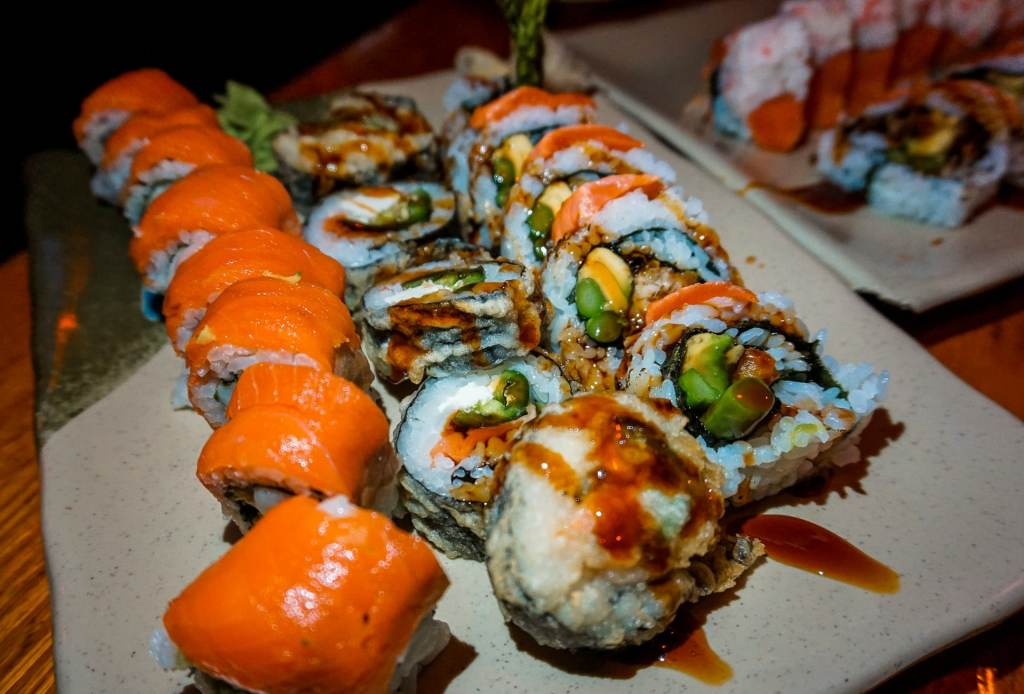 A plate full of an array of sushi rolls from Eatery Sushi in Vancouver. The sushi on the left has smoked salmon on top. The middle and right sushi has asparagus, avocado, and crab meat.