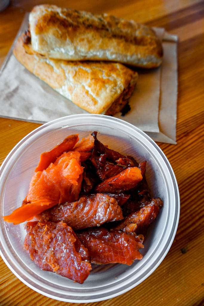 A plastic cup full of smoked candied salmon pieces from Longliner Seafood at Granville Island Public Market with two salmon puffs in the background.