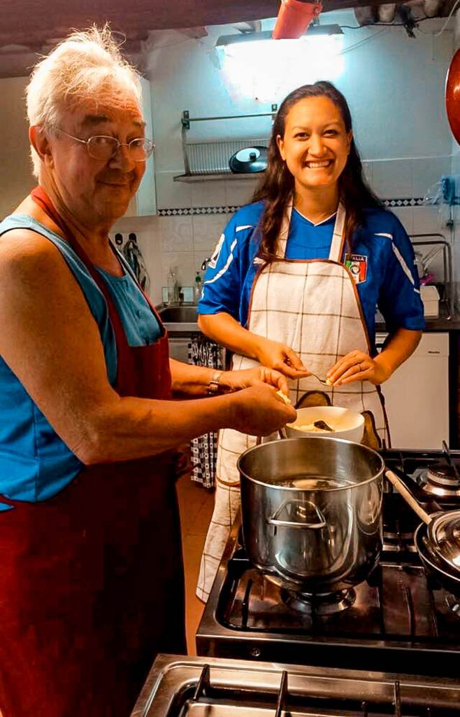 A young woman learning how to cook with her Italian host.