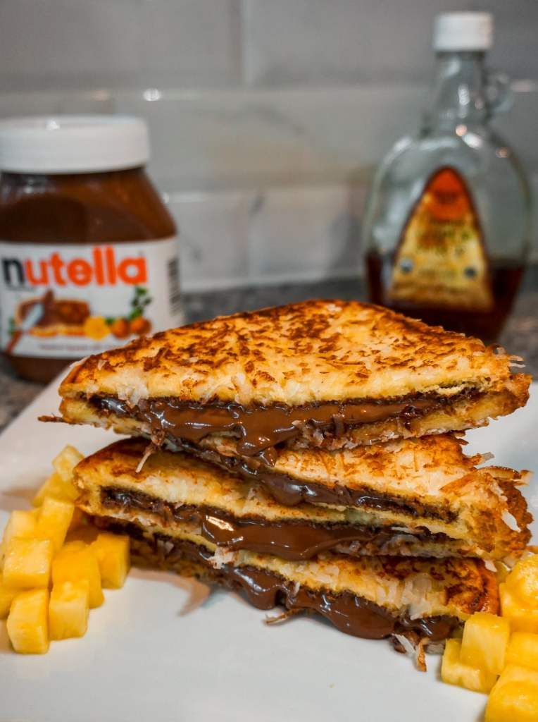 Four slices of Nutella filled French toast with coconut stacked on top of each other. A side of diced pineapple is on the plate with a jar of Nutella and maple syrup in the background.