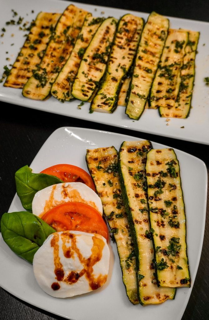 A small plate with caprese salad and Italian style grilled zucchini with a plate full of grilled zucchini in the background.
