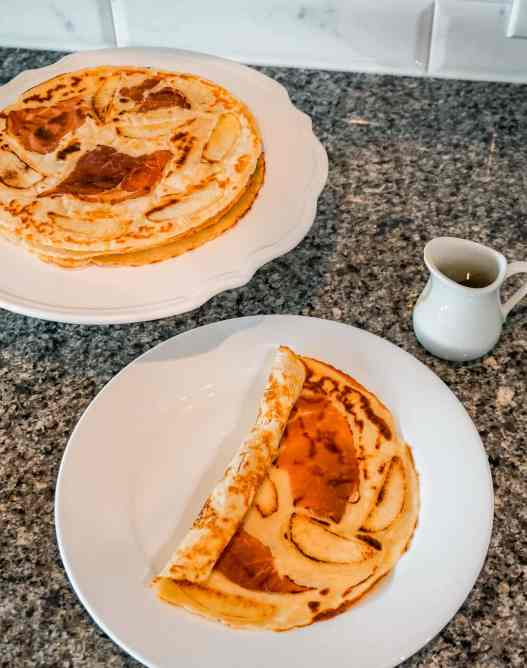 A stack full of Dutch pancakes (pannekoek) alongside a plate with the Dutch pancake folded over.