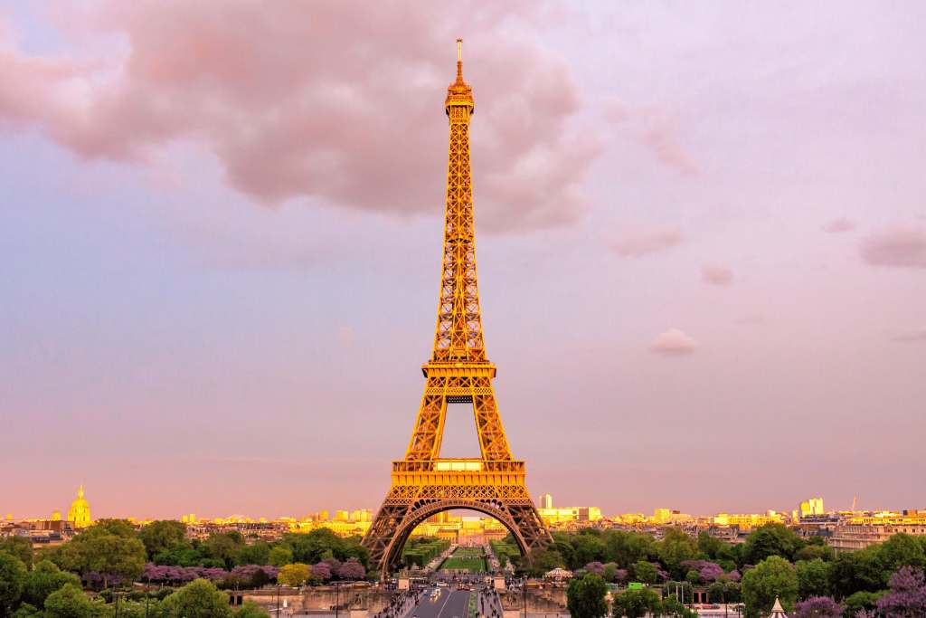 The Eiffel Tower with the golden sun shining on it in Paris, France - one of the most romantic babymoon destinations in the world.