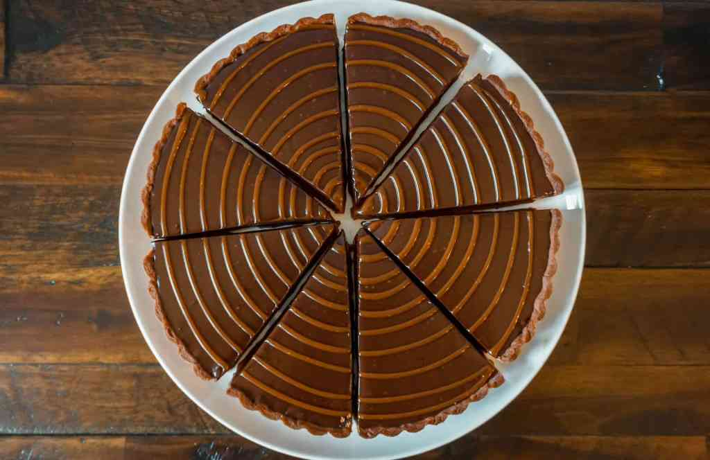 Birdseye view of a whole chocolate caramel tart sliced individually with caramel drizzled on top.