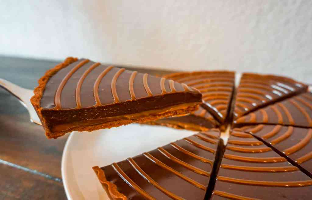 A beautiful slice of chocolate caramel tart being lifted with a pie server.