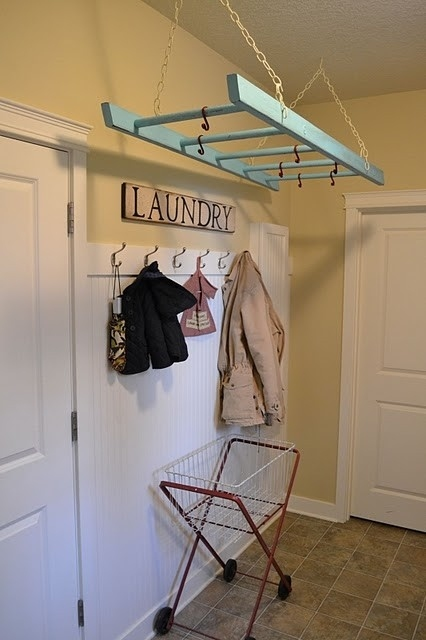 A ladder hanging overhead can be used to hang clothes in the laundry room