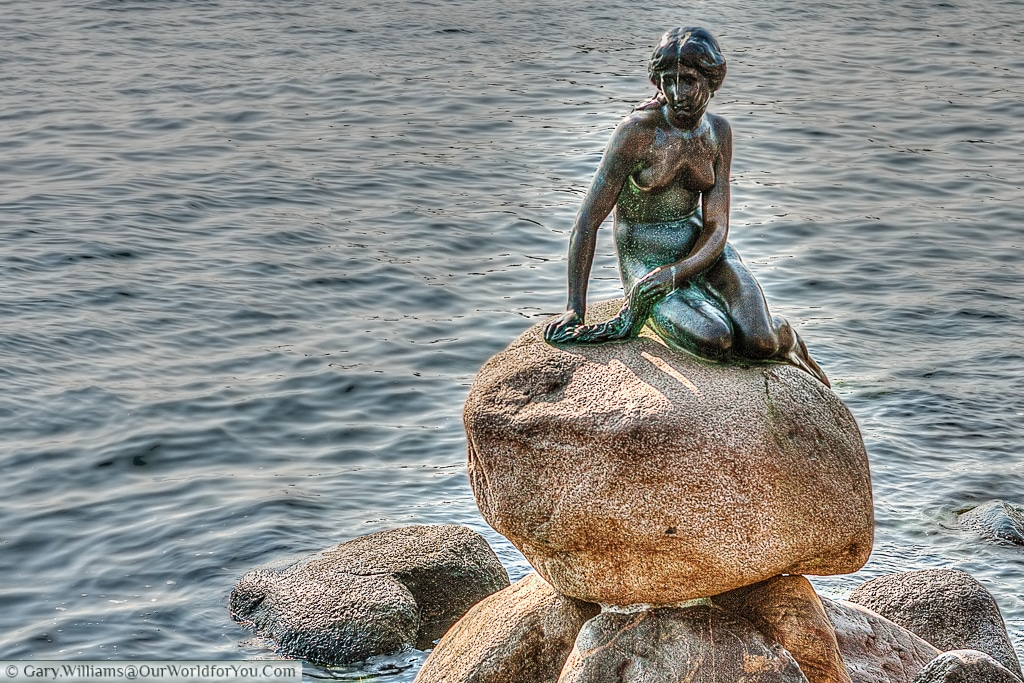 The Little Mermaid sits perched on a rock in the waterside at the Langelinie promenade, Copenhagen, Denmark