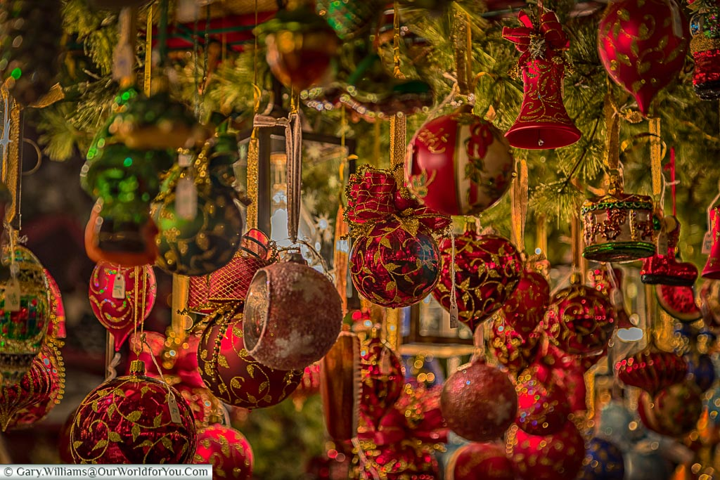 A close-up of a selection of traditional, predominately red, baubles for sale.