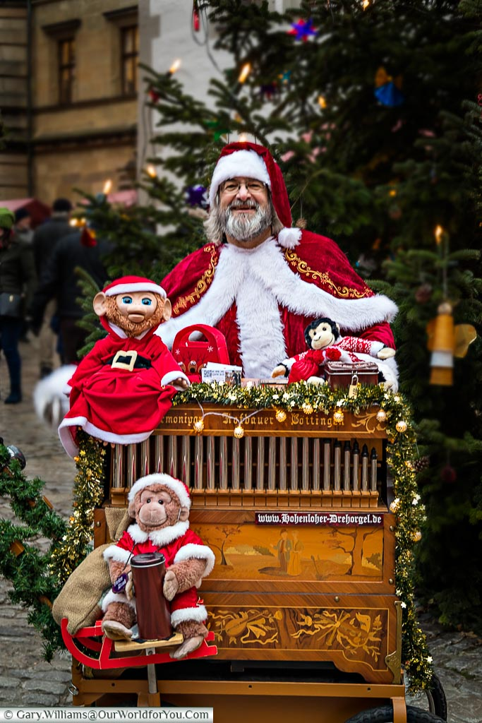 Santa playing a traditional street organ with a stuffed monkey as his collection assistant.