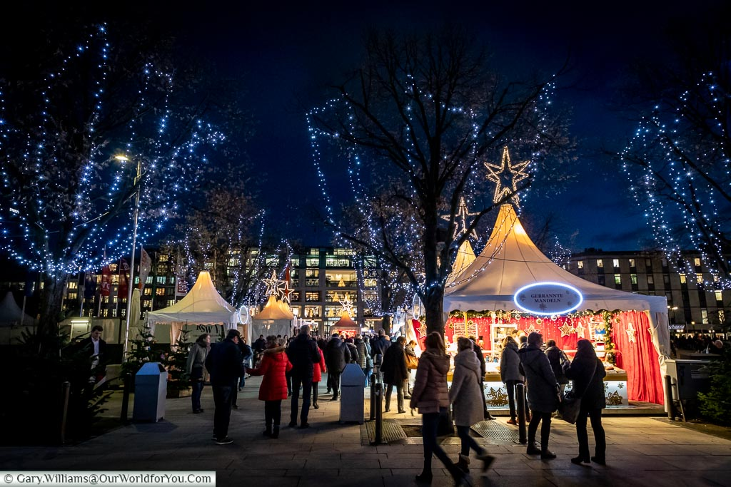 A collection of white tents that form another of Hamburg's Christmas markets along a lake edge.  The trees are decorated with blue fairy lights.