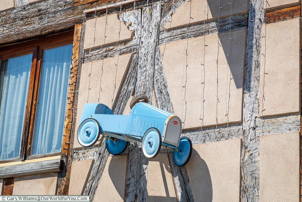 A peddle car model of a type 38  Bugatti that now hangs as a shop sign.