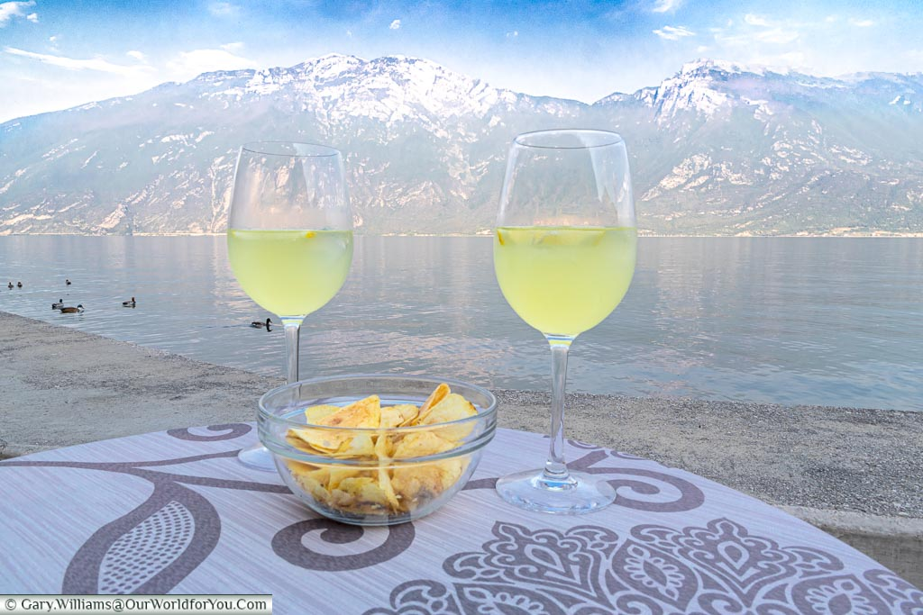 Two glasses of Limoncello Spritz, with plain crisps, next to the edge of Lake Garda with the mountains as a backdrop.