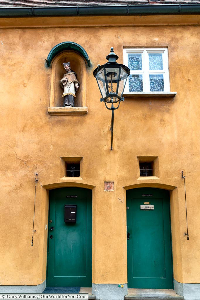 Two of the standard green doors on the ochre-coloured homes the Fuggerei.