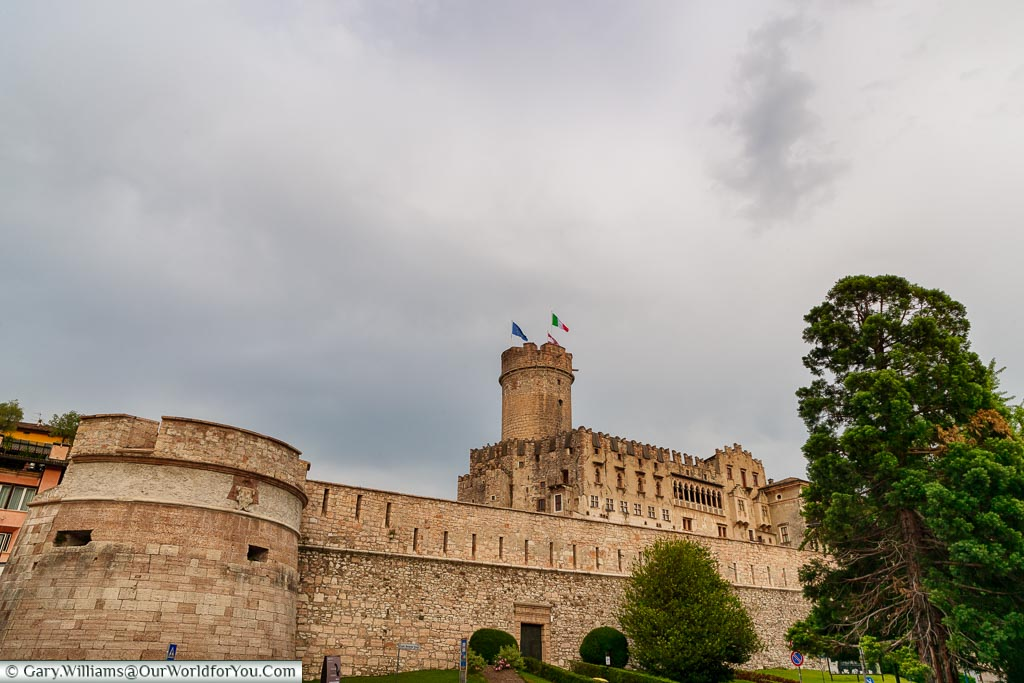 The Buonconsiglio Castle, and its surrounding walls, on an overcast evening.