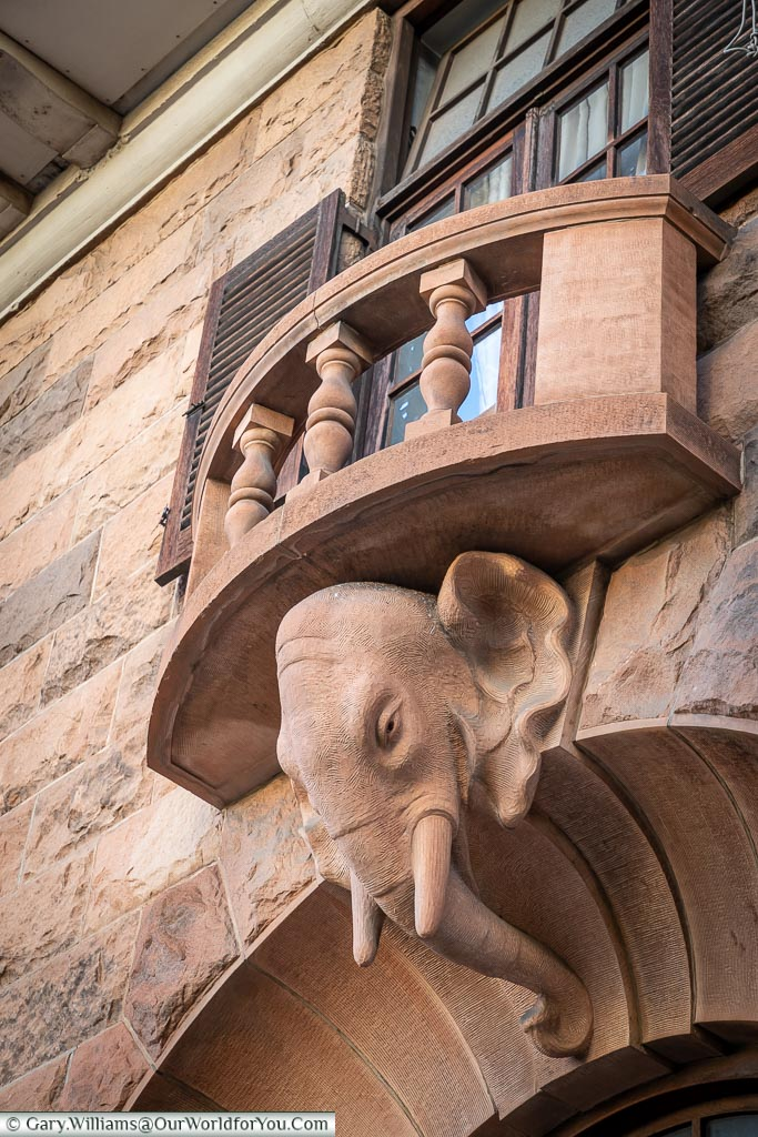 An elephant head detail carved out of stone under a balcony.