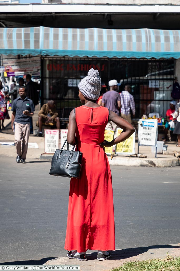 A woman in a full length, sleeveless, red dress wearing a grey wool bobble hat on a warm day in central Harare.