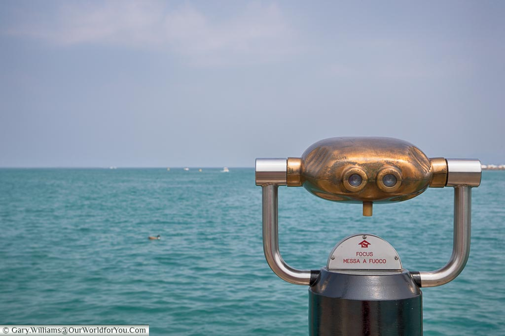 A fixed pair of brass binoculars looking over Lake Garda.