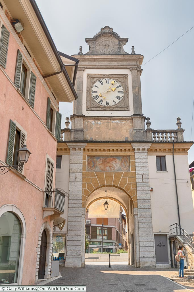 A clock tower with an arch at one end of the old town.