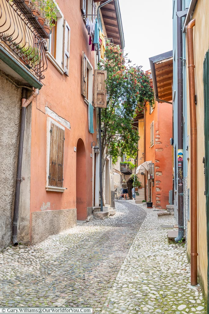 A cobbled lane lined on each side with ochre-coloured buildings.
