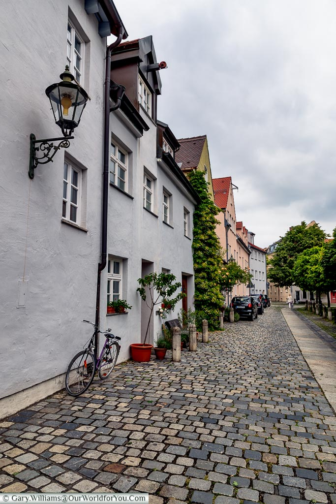 A quiet cobbled lane in front of a mixture of homes of different colours.