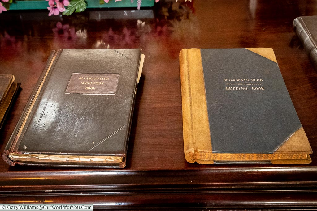 Two, rather old, leather bound, books on a wooden table. One is the Bulawayo Club Suggestion Book, the other os the Bulawayo Club Betting book.