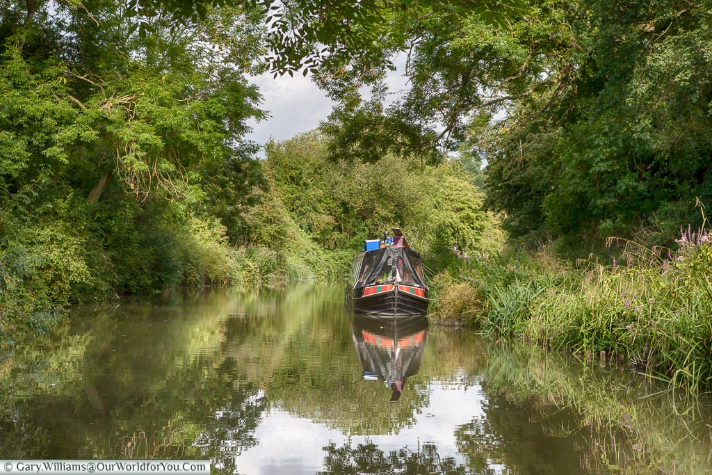 A narrow beam canal boat that is clearly somebodies home is moored up in an idyllic lush green scene as we chug along the Kennet and Avon Canal