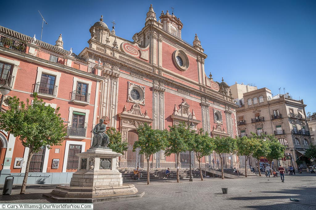 The red and white facade of the El Divino Salvador church from the Plaza del Salvador