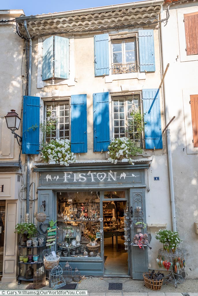 The front of a small provencal gift shop with blue shutters over the window of the upper two storeys.