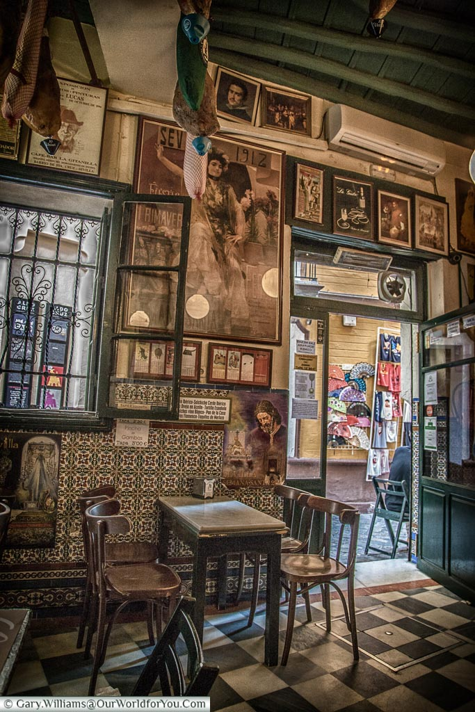 Inside the traditional Casa Placido with simple chairs & marble tabletops.  The walls are lined with framed pictures of flamenco artists & matadors.