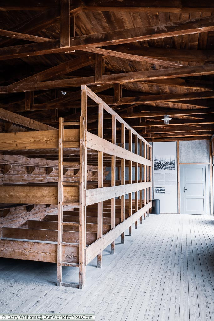 Reconstructed triple-deck cramped bunk beds in the wooden dormitories that housed the prisoners.
