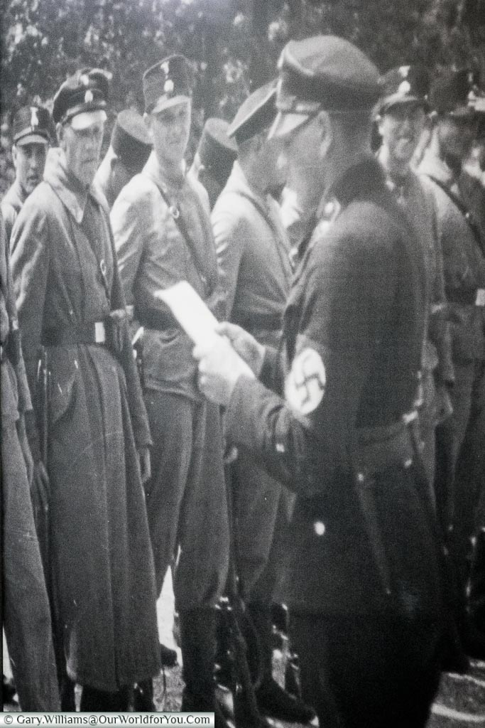 A blown-up black & white image of an officer wearing a swastika armband addressing a group camp guards.