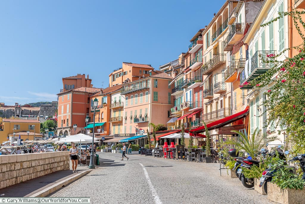 A street view of the quayside at Villefranche-sur-Mer with its pastel-coloured buildings and quaint cafés.