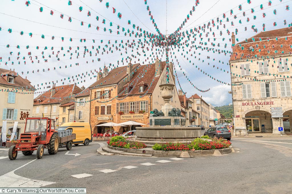 The fountain, acting as a roundabout in the centre of Arbois.  Bunting leads from all corners of the square to meet at the fountain.
