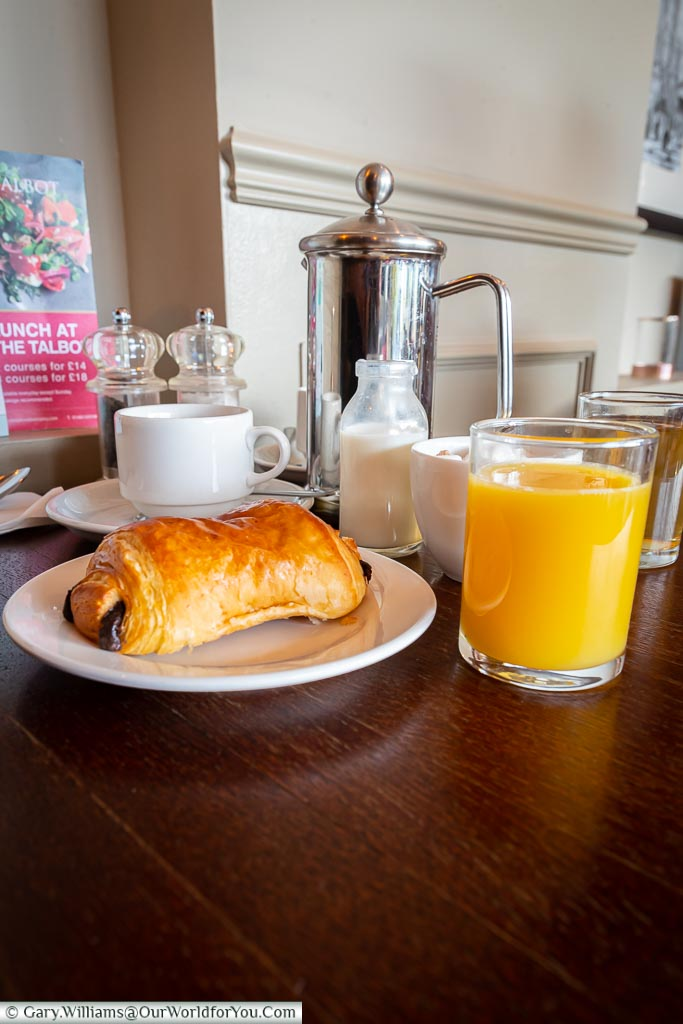 Janis's breakfast of a croissant, a coffee, and an orange juice.